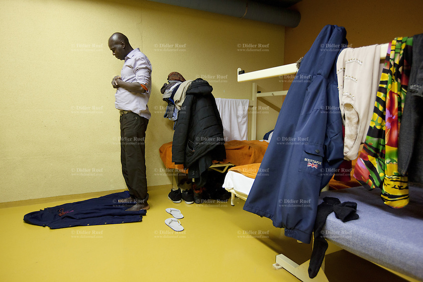 Switzerland. Geneva. A homeless black muslim man from Africa is praying near his bed in the fallout shelter Richemont. The bunker was constructed as civil defense measures during the Cold War and is a unit of the Civil Protection. Switzerland is unique in having enough nuclear fallout shelters to accommodate its entire population. 7.02.2014 © 2014 Didier Ruef