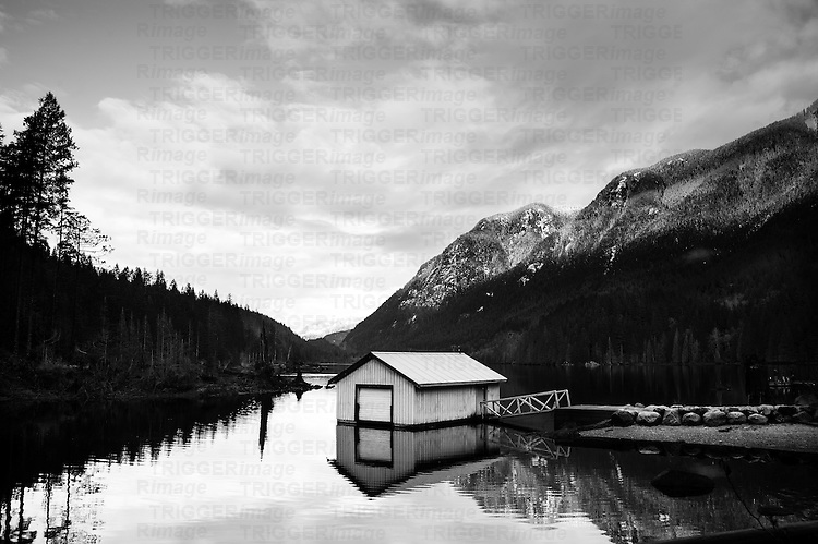 A little white house floating on a lake with snow covered mountains in background.