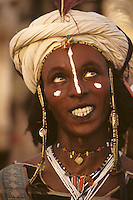 Akadaney, Niger, Africa - Fulani Wodaabe Dancer at Geerewol, with Facial Scarification.  A participant in what westerners often call the male beauty contest, in which the whiteness of the eyes and the teeth is an important factor in appealing to the female spectators.