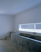 A long low window reinforces the length of an unusual custom-made concrete bath designed for two to sit opposite each other