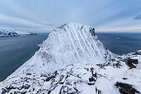 Nonhammarenveggen mountain peak rises from the sea in winter, Vestvågøy, Lofoten Islands, Norway
