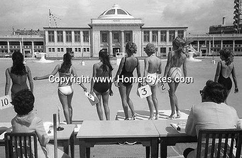 BLACKPOOL, LANCASHIRE, ENGLAND ? 1970: Contestants in one piece bathing costumes as well as one girl in a white bikini line up with their backs to the male and female judges. The finals of the annual Miss Blackpool Beauty competition are held at Blackpool Lido every summer.