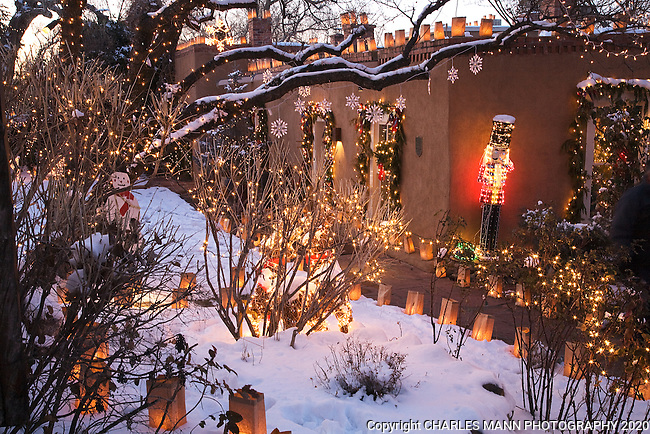 Paper bag faralitos and twinkling lights in the trees create a festive atmosphere during the annual Christmas Eve walk on Canyon Road in Santa Fe