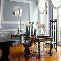 The dining room of this Paris apartment is a treasure trove of furniture and objects from all styles and periods including two chairs by Charles Rennie Mackinstosh