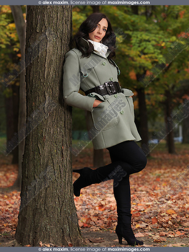 Fashionably dressed for autumn season woman wearing a green coat, leaning against a tree in a park