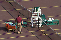 A man cleans up the courts after a tennis match