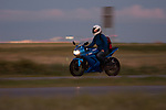 A woman rides her Kowasaki Motorcycle at dusk and notices the photographer