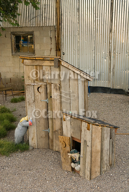 Two wooden outhouse models with stuffed animals, corrugated metal building, Nevada