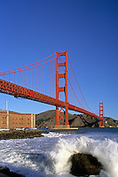 California, San Francisco, Golden Gate Bridge and Fort Point, surf on rocks