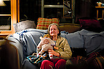 An elderly women plays with a doll. .