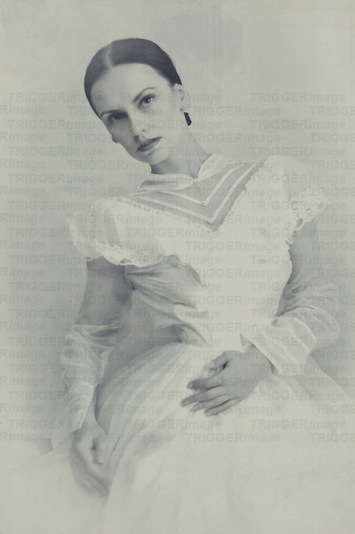 A monochrome image of a young woman in Victorian dress sitting in front of a wall
