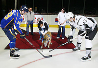 A retired service dog delivers the game puck to Peoria Rivermen's Adam Cracknell, left, and San Antonio Rampage's Nolan Yonkman, right, before an AHL hockey game, Saturday, Jan. 21, 2012, in San Antonio. (Darren Abate/pressphotointl.com)