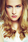Close portrait of young woman with blonde hair and serious look