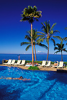 Tourists enjoy the sun and a relaxing swim at the Wailea Marriott (the old Intercontinental Hotel), with tall palms overhead and a scenic view of the island of Lanai in the background.