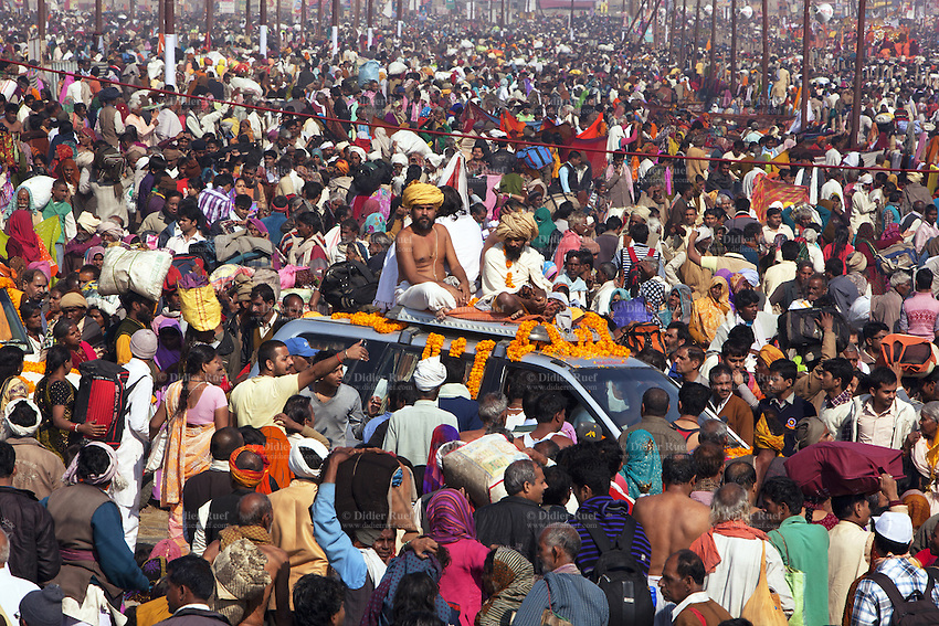 """India. Uttar Pradesh state. Allahabad. Maha Kumbh Mela. Seers and gurus seated on a four wheel drive vehicle on the day of Mauni Amavasya Snan (Royal bath for Dark moon). The ritual """"Royal Bath"""" is timed to match an auspicious planetary alignment, when believers say spiritual energy flows to earth. The Kumbh Mela, believed to be the largest religious gathering is held every 12 years on the banks of the 'Sangam'- the confluence of the holy rivers Ganga, Yamuna and the mythical Saraswati. In 2013, it is estimated that nearly 80 million devotees took a bath in the water of the holy river Ganges. The belief is that bathing and taking a holy dip will wash and free one from all the past sins, get salvation and paves the way for Moksha (meaning liberation from the cycle of Life, Death and Rebirth). Bathing in the holy waters of Ganga is believed to be most auspicious at the time of Kumbh Mela, because the water is charged with positive healing effects and enhanced with electromagnetic radiations of the Sun, Moon and Jupiter. The Maha (great) Kumbh Mela, which comes after 12 Purna Kumbh Mela, or 144 years, is always held at Allahabad. Uttar Pradesh (abbreviated U.P.) is a state located in northern India. 10.02.13 © 2013 Didier Ruef"""
