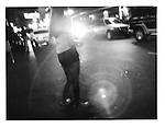 Street prostitute swallowed in the headlights of a passing car on Mabini Street, Ermita, Manila, Philippines.