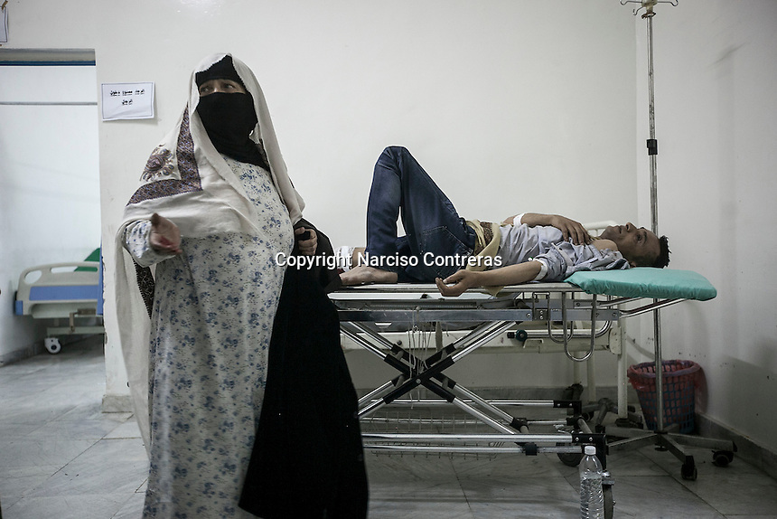 July 03, 2015 - Sana'a, Yemen: A civilian lays on a trolley as he receives medical treatment after a fighter jet from the Saudi-led coalition bombed the civilian neighborhood of Jaraf located in Zoubeiri area in the Yemeni capital of Sana'a. The neighborhood was bombed twice during an attemp to hit the house of the leader Houthi Brigadier Ali Al Nashri. The bombs missled the target killing many civilians, among the dead were one woman and two children. (Photo/Narciso Contreras)