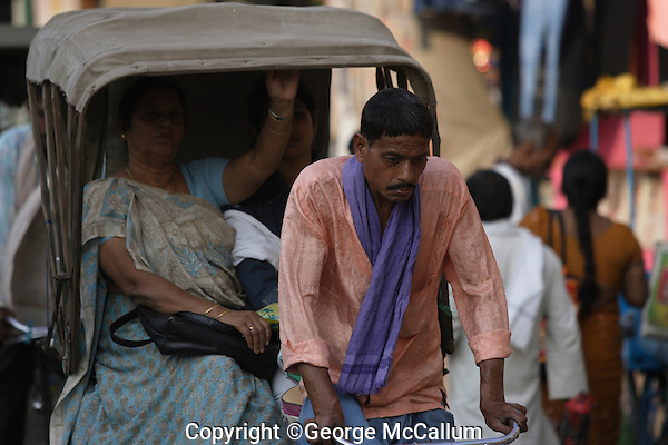 Rickshaw wallah or puller with Customer in back. Varanasi, Uttar Pradesh, India