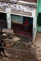 A man walks past a brothel while a brothel owner stands in front of her brothel in the Shivdaspur red light area in Varanasi, Uttar Pradesh, India on 20 November 2013. Guria had raided the red light area in 2005, rescuing 57 underaged girls, seizing the operations of 10 brothels, and jailing 39 brothel owners, traffickers and pimps, and Guria continues to run a non-formal education center in the middle of the red light district for the sex workers' children.