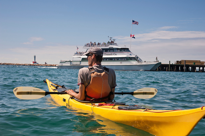 A kayaker paddles amongst the busy ferry traffic of Mackinac Island Michigan on Lake Huron.