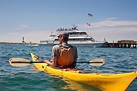 A kayaker paddles amongst the busy ferry traffic of Mackinac Island Michigan on Lake Huron.