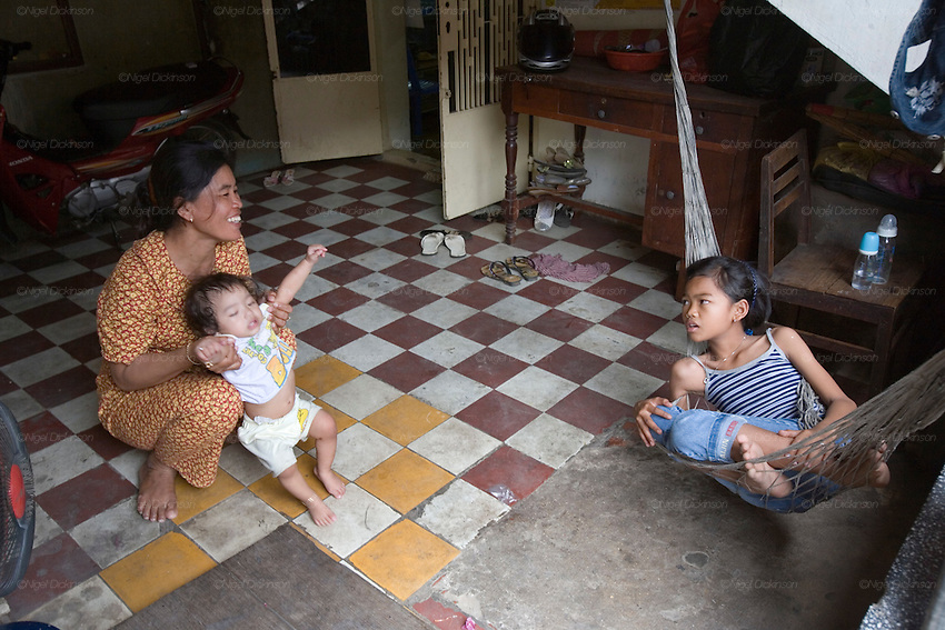 Chanthy plays in the stairwell of the municipal housing block where she lives..Chanthy, a young girl, learns the Apsara traditional Khmer dance style, at the School of Beaux Arts outside Phnom Penh. This dance style is particularly inspired by thousands of Apsara statues found at Angkor Wat and performed by the Cambodia Royal Ballet. Chanthy lives with her family in Phnom Penh, her father is a policeman, and her family lives in a municipal apartment block surrounded by other families. Chanthy has good friends including a Chinese girl who is mentally handicapped and lives next door. She loves to visit Phnom Penh city and sites with her mother and father, on his scooter.