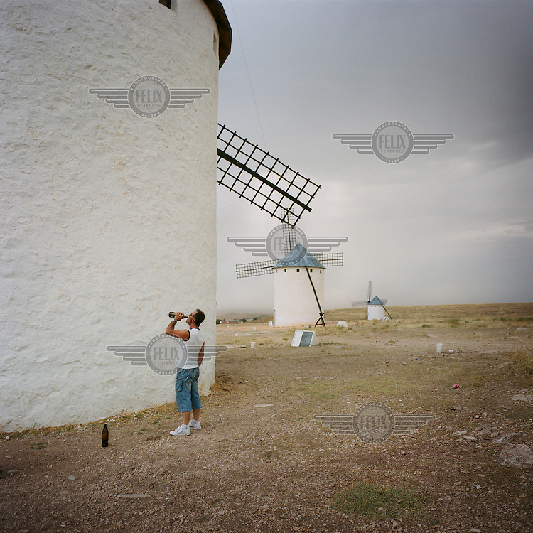 A man, standing next to a windmill, drinks beer from a bottle. Campo de Criptana was known as the 'The heart of giants' in reference to its windmills and is the supposed inspiration for  Miguel de Cervantes' Don Quixote.