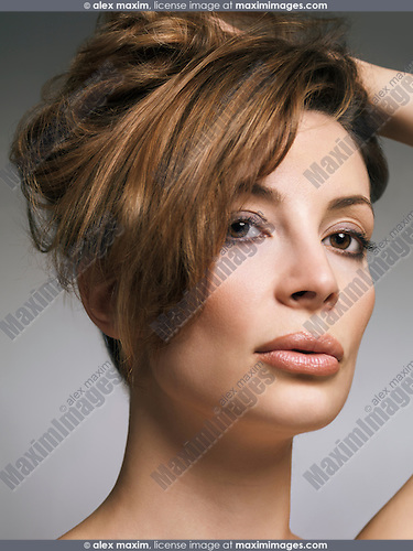 Beauty portrait of a woman with light brown hair in updo and natural makeup in her early thirties isolated on gray background