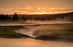 Wyoming, Yellowstone National Park, Madison. Sunrise over the steaming Madison River. A photographer in the mist.