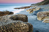 Pastel colours of dusk on beautiful rocky beach with limestone formations at Paturau on west coast of South Island, Nelson Region, New Zealand