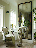 In the master bathroom, an American 1850s gilt mirror and an antique sink with Dornbracht fittings are reflected in a custom-made mirror; the armchair is from France and the walls are painted in Benjamin Moore's Waterbury Cream