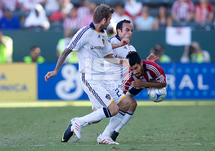 Landon Donovan and David Beckham of the LA Galaxy team up to take out Chivas USA midfielder Paulo Nagamura. The LA Galaxy and Chivas USA played to 2-2 draw during a MLS Western Conference playoff game at Home Depot Center stadium in Carson, California on Sunday November 1, 2009...