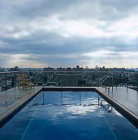 A roof-top swimming pool with a view over the New York city skyline