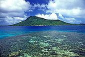 A large coral reef surrounded by calm turquoise water fronts the lush green mountains topped with fluffy clouds on the island of Chuuk in Micronesia.