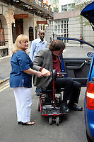 RICHARD KIEL.Having a Bond reunion lunch at The Ivy Club this afternoon, London, England..April 26th, 2010.full length grey gray suit jacket red top black trousers sitting wheelchair jaws pofile .CAP/DYL.©Dylan/Capital Pictures.