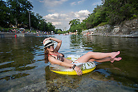 Woman with tanned body sitting on yellow air mattress at Barton Springs Pool in summer and having fun. Outdoor portrait of happy girl with sunglasses and fedora hat.