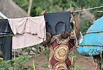 Displaced by war, a woman hangs laundry to dry in the Makpandu refugee camp in Southern Sudan, 44 km north of Yambio, where more that 4,000 people took refuge in late 2008 when the Lord's Resistance Army attacked their communities inside the Democratic Republic of the Congo. Attacks by the LRA inside Southern Sudan and in the neighboring DRC and Central African Republic have displaced tens of thousands of people, and many worry the attacks will increase as the government in Khartoum uses the LRA to destabilize Southern Sudan, where people are scheduled to vote on independence in January 2011. Catholic pastoral workers have accompanied the people of this camp from the beginning.