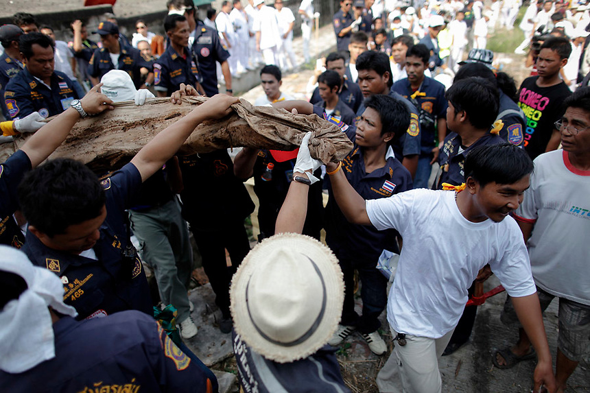 People carry unclaimed human remains taken out of a grave during a Thai Chinese ceremony at the Mang Teung Sua Jung Cemetery in Chonburi province southeast of Bangkok March 18, 2012. Every 10 years, hundreds of people wearing white, a customary colour for funerals and visiting temples, gather at this cemetery to exhume and cremate corpses as they believe they are helping the dead who have no friends or relatives. The ashes of the unclaimed bodies are spread on the sea to make room at the burial ground for more unclaimed bodies in the coming years. The tradition originated 90 years ago after diseases like Malaria killed many Thais of Chinese descent living in Chonburi.  REUTERS/Damir Sagolj (THAILAND)