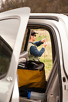 An angler is seen through the open door of a vehicle as he rigs up his fly rod.