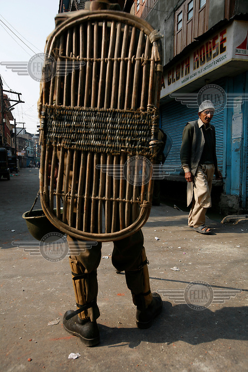 An old man is allowed to go to Friday prayer as paramilitary police enforce a curfew imposed to stop separists gather for a political demonstration in Srinagar, Kashmir, India. © Fredrik Naumann/Felix Features