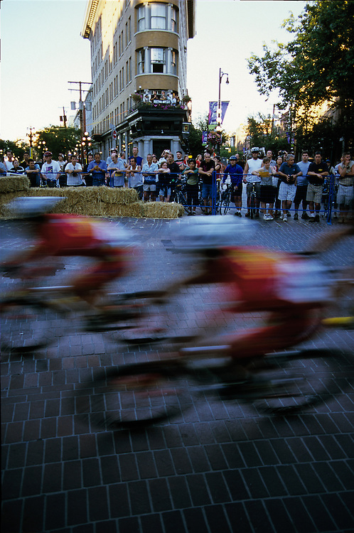 Cyclists racing by on brick pavement in Gastown during the annual Tour de Gastown bicycle race in Vancouver, BC.