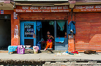 A merchant with her infant in front of her store in Thamel, Nepal