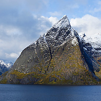 Mountain peak rises from Kjerkefjord, Lofoten islands, Norway