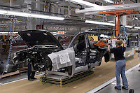 A woman on the Nissan production line uses a robotic arm to install the interior of the new Armada. For Nissan North America.