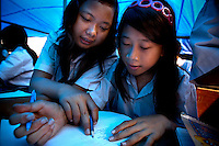 Seventh grade students, 15 year old Nasridah (left) and 13 year old Lanjar Arum Sari during an English class at the new temporary location of Kartini Emergency School in a makeshift tent set up on an empty lot in North Jakarta. Since the early 1990s, twin sisters Sri Rosyati (known as Rossy) and Sri Irianingsih (known as Rian) have used their family inheritance to set up and run 64 schools in different parts of Indonesia, providing primary education combined with practical skills to some of the country's most deprived children.