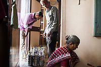 Archana's husband (left) and father-in-law (center) prepares tiffin containers, as she continues to work with Dr. Nayana Patel, catering specially prepared tiffin meals to the surrogates and Akanksha IVF and Surrogacy clinic staff, which she prepares in her house with her family in Anand, Gujarat, India on 11th December 2012. Photo by Suzanne Lee / Marie-Claire France