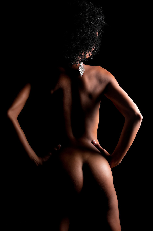 Sensual latin woman posing nude in dim light.