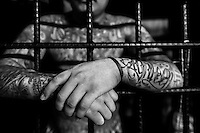 A Mara Salvatrucha gang member is seen behind the bars of cells in a detention center in San Salvador, El Salvador, 20 February 2014. During the last two decades, Central America has become the deadliest region in the world that is not at war. According to the UN statistics, more people per capita were killed in El Salvador than in Iraq, in recent years. Due to the criminal activities of Mara Salvatrucha (MS-13) and 18th Street Gang (M-18), the two major street gangs in El Salvador, the country has fallen into the spiral of fear, violence and death. Thousands of Mara gang members, both on the streets or in the overcrowded prisons, organize and run extortions, distribution of drugs and kidnappings. Tattooed armed young men, mainly from the poorest neighborhoods, fight unmerciful turf battles with their coevals from the rival gang, balancing between life and death every day. Twenty years after the devastating civil war, a social war has paralyzed the nation of El Salvador.