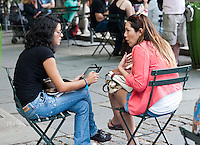 Two women talking in Bryant Park in New York, one with her tablet computer, on Thursday, June 7, 2012 (© Richard B. Levine)