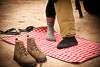 An angler uses a red checkered blanket to cover the ground while he changes into fishing waders and wading boots.
